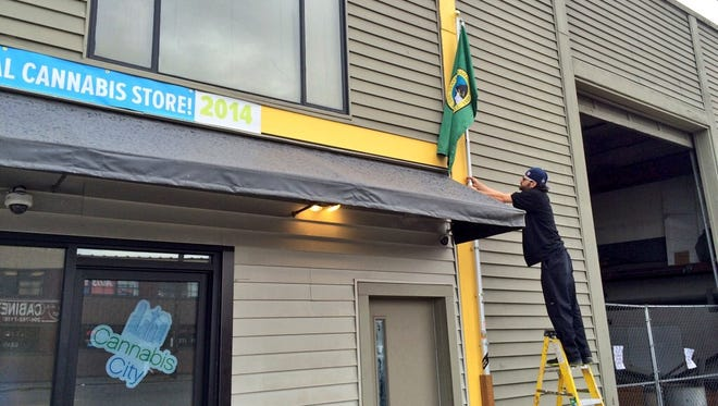 "Security guard Chris Swanson takes down the flag outside Seattle marijuana store Cannabis City on Sept. 23, signifying the store has run out of flower or ""bud,"" and only has less-desirable products available."