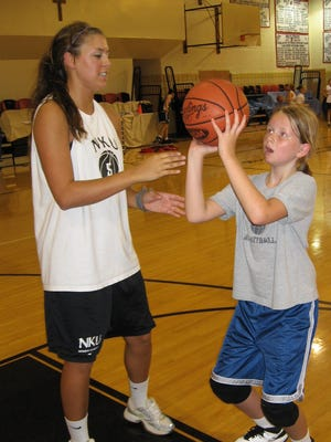 Holy Cross graduate Rachel Lantry works with Ally Ward on form shooting during the Holy Cross High School girls basketball camp in 2009.