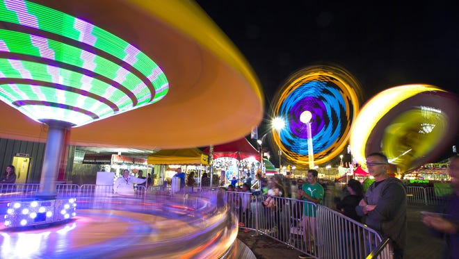 Lights from the Motorcycles, Speed and Zero Gravity rides at the Arizona State Fair paint the night sky.