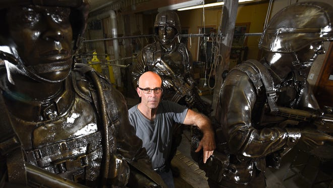 Alan Cottrill stands with some of the statues that will be placed at the Global War on Terror Memorial Plaza at the National Infantry Museum and Solider Center in Georgia.