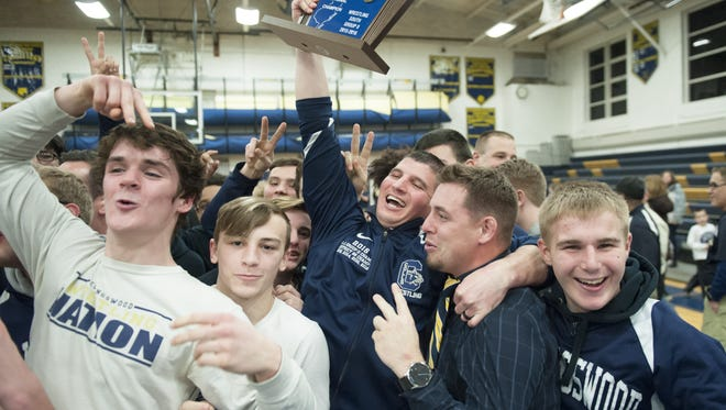 Collingswood High School wrestling coach Dechlin Moody hoists the trophy after Collingswood defeated Haddonfield to win the South Jersey Group 2 wrestling championship at Collingswood High School on Friday.  02.10.17