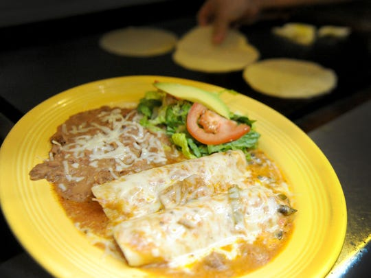Chili verde enchiladas are plated for serving at El Capricho Restaurant in Santa Paula.