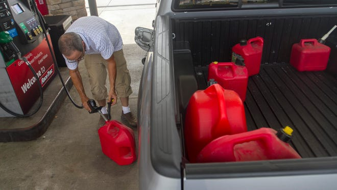 Hector Diaz of Miami fills up gas cans in Fort Myers Thursday to go back to Miami to be with his wife during Hurricane Matthew.