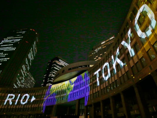 """FILE - In this July 24, 2017, file photo, images are illuminated on the Tokyo Metropolitan Government building during the Tokyo 2020 flag tour festival for the 2020 Games in Tokyo. Tokyo has billed itself as a """"safe pair of hands"""" and is everything that Rio de Janeiro wasn't during the last Summer Olympics. Rio left behind scandals, millions in unpaid bills, and empty """"white elephant"""" venues. (AP Photo/Shizuo Kambayashi, File)"""