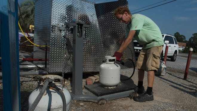 Justin Franks, an employee of Hall's Hardware and Lumber in Milton, refills propane tanks for customers on Tuesday, Sept. 5, 2017. Store owner Wade Allen said plywood, gas cans, water, generators and propane were among the most sought-after items as residents braced for Hurricane Irma.