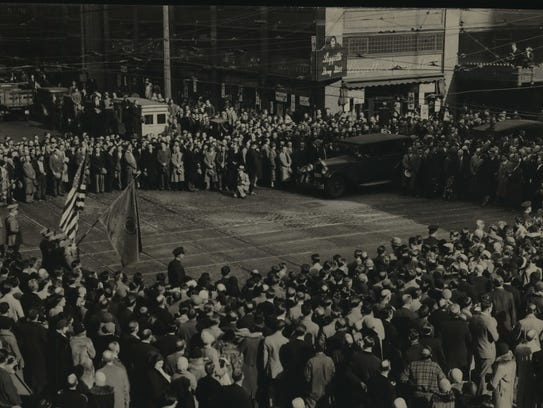 Milwaukeeans gather at N. 3rd St. and W. Wisconsin Ave. to mark Armistice Day on Nov. 11, 1930. The firing squad shown in action was commanded by Lt. Earl Fonteine.This photo was published in the Nov. 11, 1930, Milwaukee Journal.