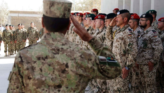 Members of the Afghan National Civil Order Police, Afghan Armed Forces and German armed Bundeswehr forces attend the handover ceremony of a German base to Afghan armed forces in Kunduz Oct. 6, 2013.