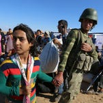 A Turkish soldier holds the hand of Sidra, 12, a Kurdish refugee girl from Kobani who lost her parents after their arrival at the Turkey-Syria border near Suruc, Turkey, on Tuesday, Sept. 30, 2014. U.S.-led coalition airstrikes targeted Islamic State fighters pressing their offensive against a Kurdish town near the Syrian-Turkish border on Tuesday in an attempt to halt the militants' advance, activists said.