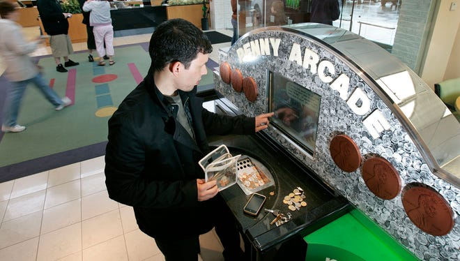 A customer puts change in a Penny Arcade coin counting machine at a TD Bank branch in Fairless Hills, Pa.