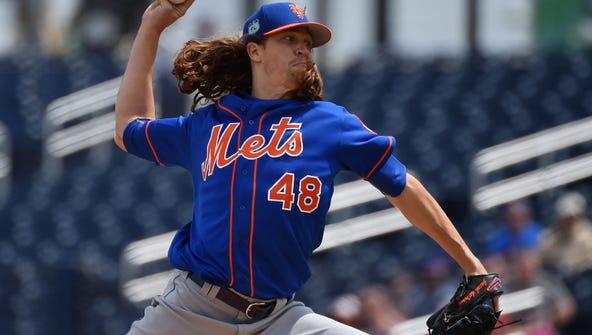 Jacob deGrom pitches earlier in camp.