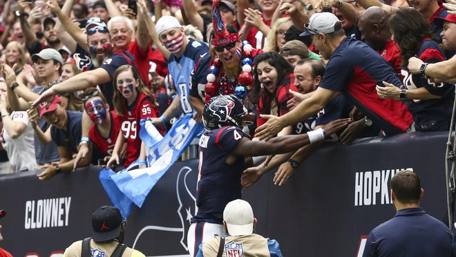 Texans QB Deshaun Watson leaps into the stands at NRG Stadium after scoring a touchdown against the Titans on Sunday. Watson could be one of the top waiver-wire additions in fantasy football this week.