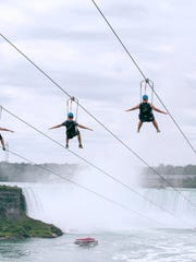 Tourists suspended above the water from zip lines make their way at speeds of up to 40 mph toward the the mist of the Horseshoe Falls, on the Ontario side of Niagara Falls.