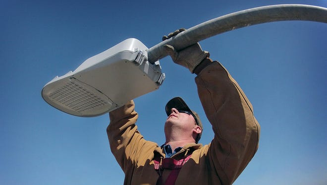 Pete Ermis installs a new energy-efficient LED light fixture on a street light fifty feet above the Emmanuel Davis Overpass. The City of Wichita Falls, Texas, has replaced about 25% of the approximately 8,000 street lights in town.