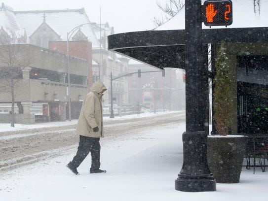 A man makes his way across 2nd Street in Downtown Evansville