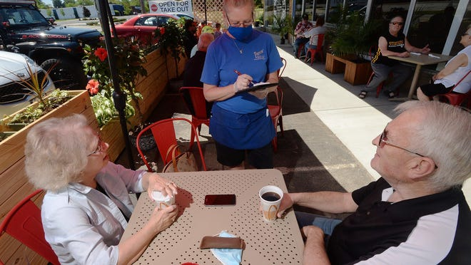 Linda Franklin, left, and her husband Steve Franklin, both 68, order lunch from Panos' Restaurant server Eleanor Mello, 59, in the new outdoor patio area on Monday. The Franklins said they visit the popular spot nearly every day.