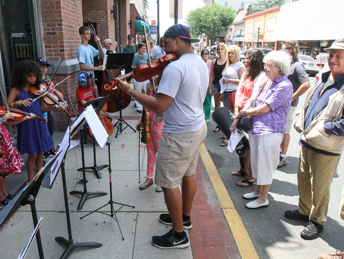 "Red Bank, NJ - Elijiah Gray, center, leads students in Red Bank's school ""strings"" program as they perform on the sidewalk on Monmouth Street. The Red Bank Public School District recently cut its ""strings"" program, and the Red Bank Borough of Education Foundation is attempting to raise $85,000 to reinstate the program."