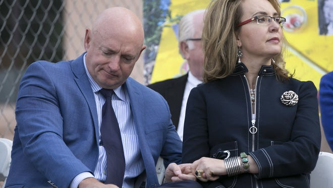 Former  U.S. Rep. Gabrielle Giffords holds the hand of her husband, Mark Kelly, during the memorial dedication for Tucson's January 8th Memorial at El Presidio Park in Tucson on Monday, Jan. 8, 2018. The dedication was held on the seven-year anniversary of the Tucson mass shooting.