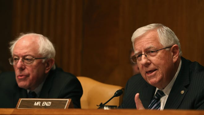 Senate Budget Committee Chairman Mike Enzi, R-Wyo., right, speaks next to Sen. Bernie Sanders, I-Vt., during a hearing on Capitol Hill on Tuesday, Feb. 3.