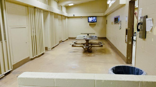 Individual jail cells, left, and a common living area, center, in the Tompkins County Jail.