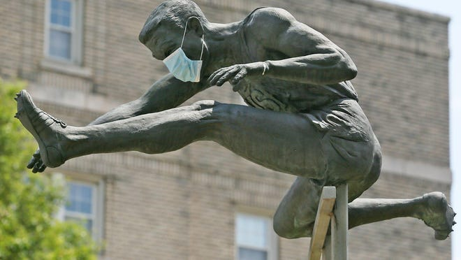 """A statue of Olympic hurdler Glenn """"Jeep"""" Davis wears a COVID-19 mask outside Barberton Public Library on Tuesday, June 2, 2020. Davis (1934-2009) won three gold medals in the 1956 and 1960 Olympics."""