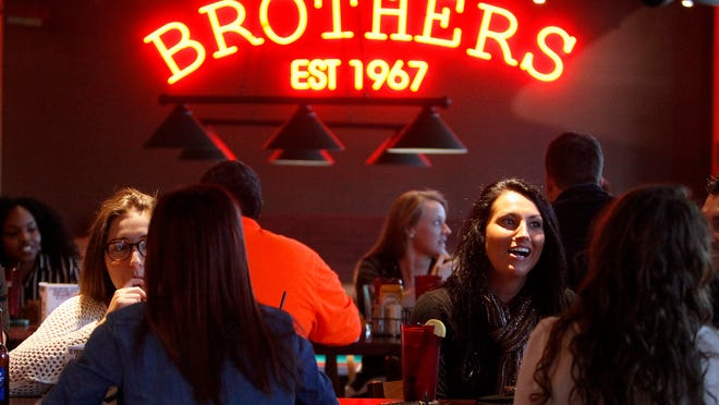 The crowd enjoys the preview event for the new Brothers restaurant in the Village Promenade on Wednesday.