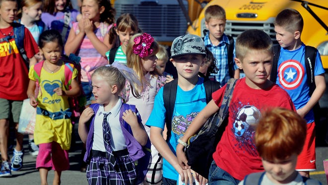 On the first day of class Wednesday at Chancellor Livingston Elementary School in Rhinebeck, students approach the main entrance after arriving on a convoy of buses.