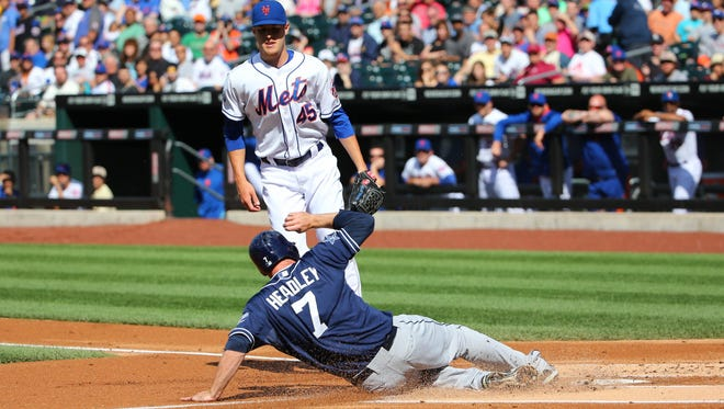 San Diego's Chase Headley, front, slides home to score on a wild pitch thrown by the Mets' Zack Wheeler in the first inning at Citi Field on Saturday.