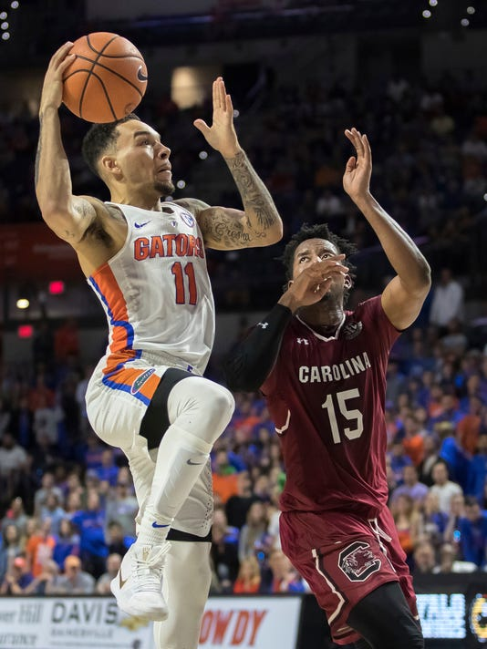 Florida guard Chris Chiozza (11) rises up for a layup as South Carolina guard Wesley Myers (15) defends during the second half of an NCAA college basketball game in Gainesville, Fla., Wednesday, Jan. 24, 2018. South Carolina won 77-72. (AP Photo/Ron Irby)