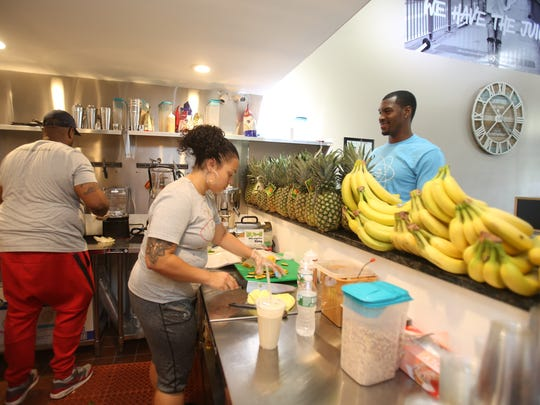 Brooklyn Nets star Sean Kilpatrick watches as Dameion White and Tanya Alvarez prepare juices for customers at The Juice Lab on Aug. 17, 2017.
