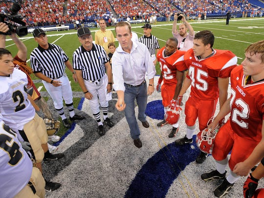 Peyton Manning flips the coin between the Fishers and