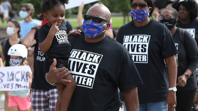 Children and parents take part in a march in solidarity with the Black Lives Matter movement in Gainesville on June 13, 2020.