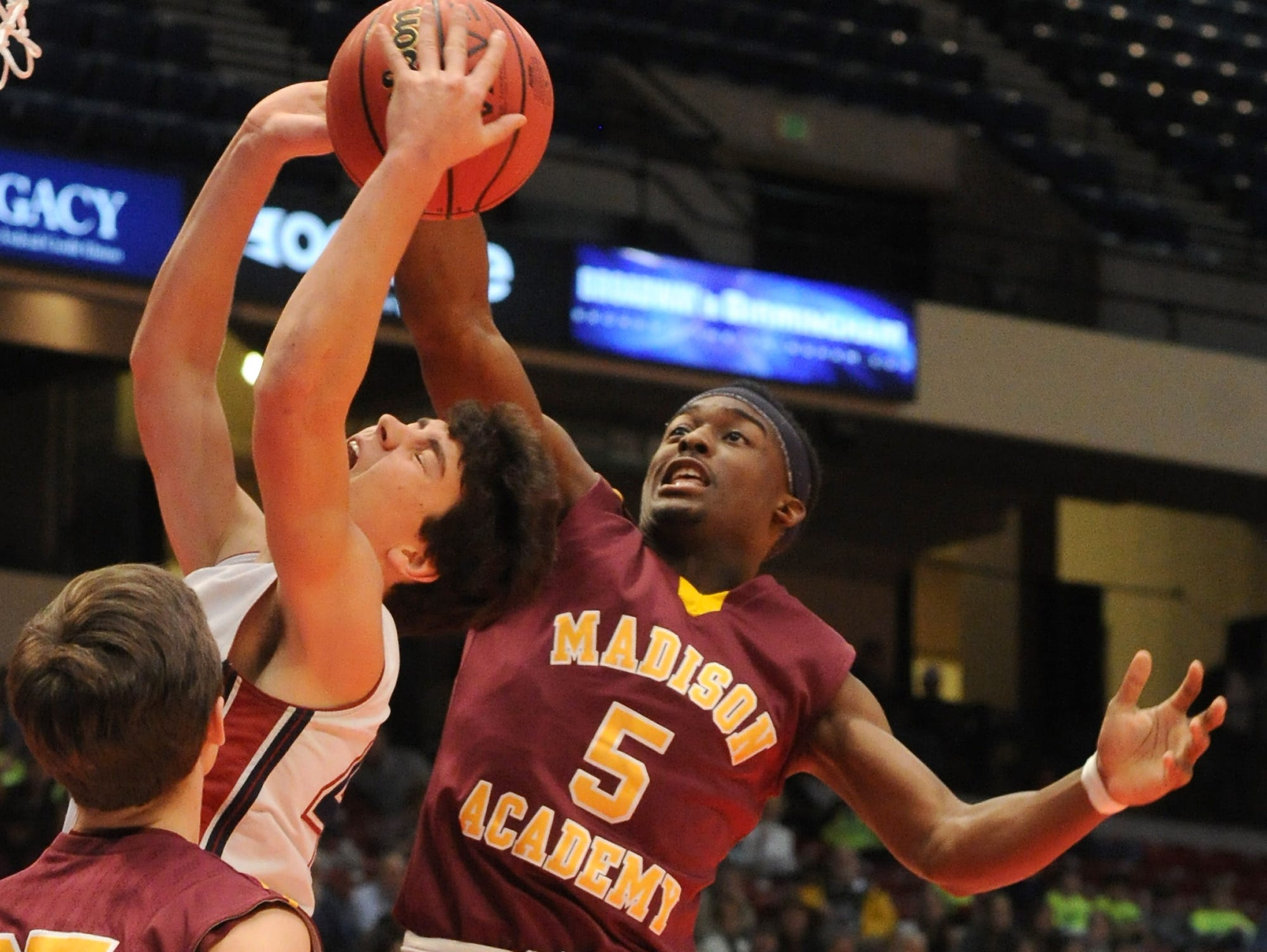 Madison Academy?s Joshua Langford blocks a shot by Montgomery Academy's Barton Lester during an AHSAA Class 3A state semifinal game on Feb. 24 in Birmingham, Ala. Madison Academy won, 66-55.