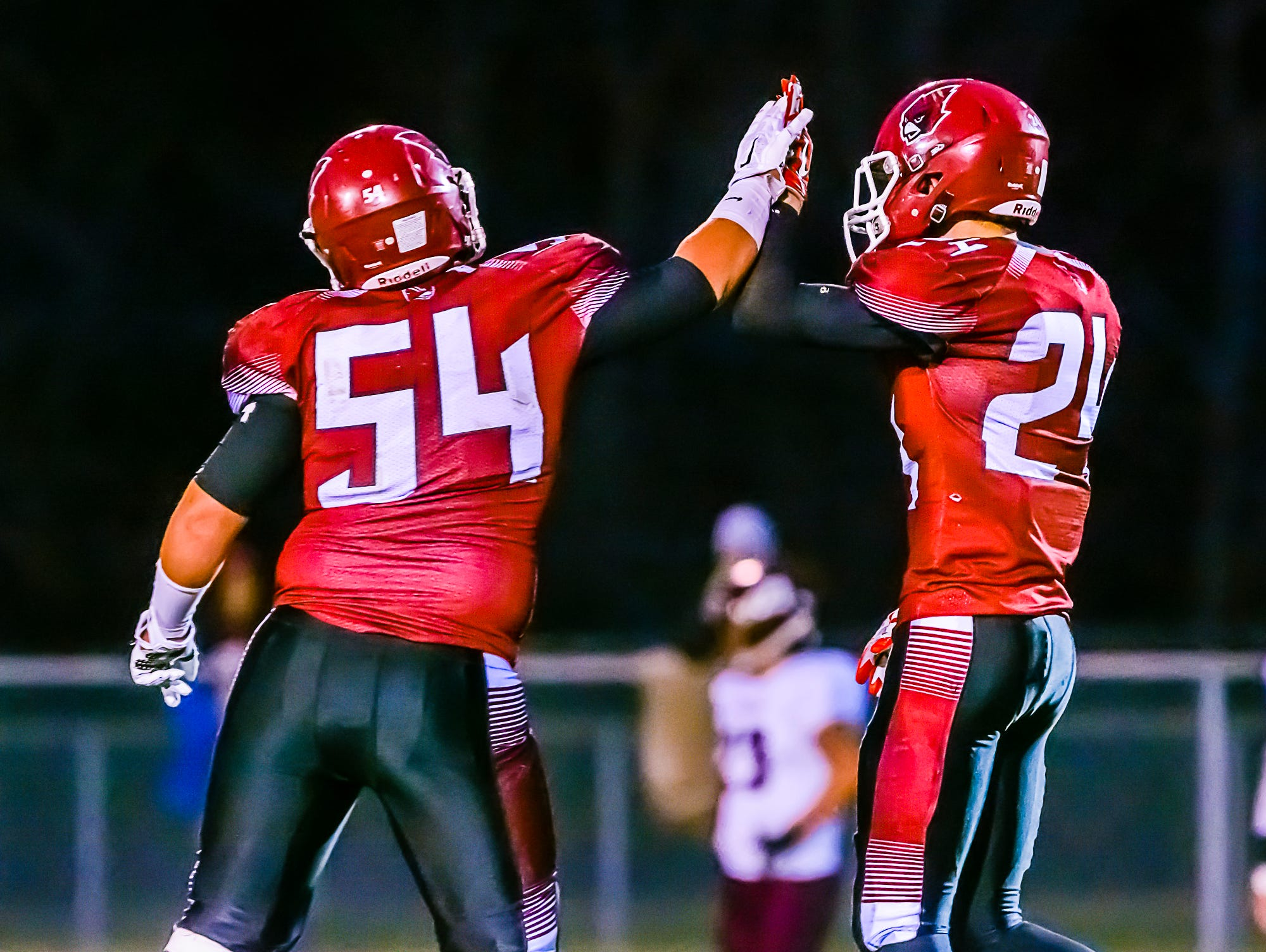 Portland defenders Dylan Goodman ,54, and Treyvin Groesser ,right, high five after bringing down a Portland runner for a loss during their game Friday.