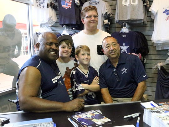 Zachariah and Hunter Bazzle, center, and friend Cedric Heidelberg, top, get their photo taken with Dallas Cowboys bus driver Emory Tyler, left, and reporter Mickey Spagnola at the Dallas Cowboys Official Pro Shop on Friday at The Outlet Shoppes at El Paso.