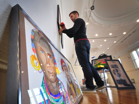 In this file photo, Matthew Clay-Robison, gallery director at Marketview Arts on West Philadelphia Street, hangs an exhibit. Bil Bowden photo