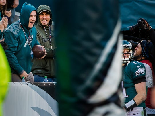 Los Angeles Angels of Anaheim outfielder Mike Trout (left) yells to Eagles quarterback Carson Wentz (right) after Wentz handed him a football following a touchdown pass to Zach Ertz in the third quarter of the Philadelphia Eagles 27-13 win over the Dallas Cowboys at Lincoln Financial Field in Philadelphia, Pa. on Sunday afternoon.