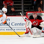 Matt Read of the Philadelphia Flyers scoes the game winning goal in overtime as Cory Schneider of the New Jersey Devils defends on Friday at Prudential Center in Newark, New Jersey. The Philadelphia Flyers defeated the New Jersey Devils 4-3.