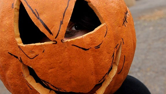 Jackson Knight, 11, peers from behind his Jack-o-Lantern mask during the Halloween festivities at Peak Community Church in Fort Collins.