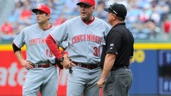 Reds manager Bryan Price (38) questions a call with first base umpire Greg Gibson during the first inning of Sunday's game at Turner Field. Price was ejected for arguing after a replay upheld a call at first base.