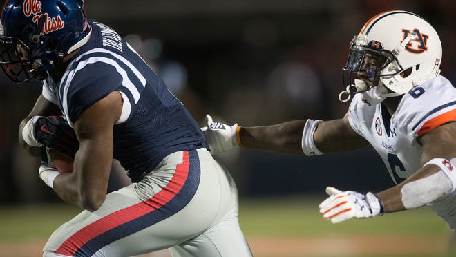 Auburn defensive back Jonathon Mincy tackles Ole Miss quarterback Bo Wallace.