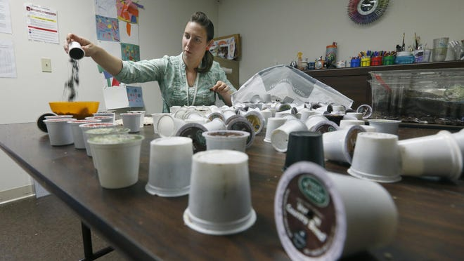 Aubrey Donovan uses coffee grounds and filters from recycled K-Cups to create her work for the first eco-art challenge at Spectrum Creative Arts LLC., in Pittsford.