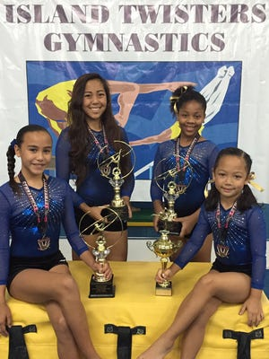 """Island Twisters Gymnastics held a gymnastics demonstration on May 3 at the Micronesia Mall. More than 140 gymnasts performed at the event, demonstrating all types of tumbling skills such as cartwheels, handstands, back-handsprings, aerials and back flips. The 2015 gymnastics awards were given out to Ariana Balagot (level 3) """"Little Shining Star Gymnast,"""" Gypsy Catling (level 4) """"Most Spirited Gymnast,"""" Qaydenz Montgomery (level 5-6) """"Most Improved Gymnast,"""" and Aisha Tangi (level 8) """"Most Valuable Gymnast."""" The gymnasts are shown with their awards.Photo courtesy of Melinda Heath"""