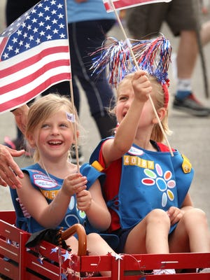 Sky Laido, left, and Grace Glazer wave Amercan flags just before the beginning of last year's Memorial Day parade in Hartand.