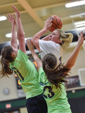 Lindsay Embly tries to shoot a basket while being guarded