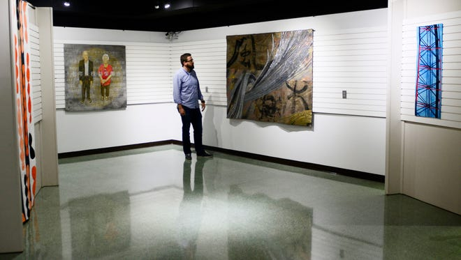 "Kevin Moore, associate curator of artifacts for the Hayes Presidential Library and Museums, looks at the ""Quilt National"" exhibit that runs through Oct. 15. Pictured, from left, are the quilts ""Transpiration"" by Leslie Bixel, ""Legislating Love"" by Kathleen Kastles, ""COSMOS#7"" by Shoko Hatano and ""Roadside Constructs"" by Virginia Abrams."