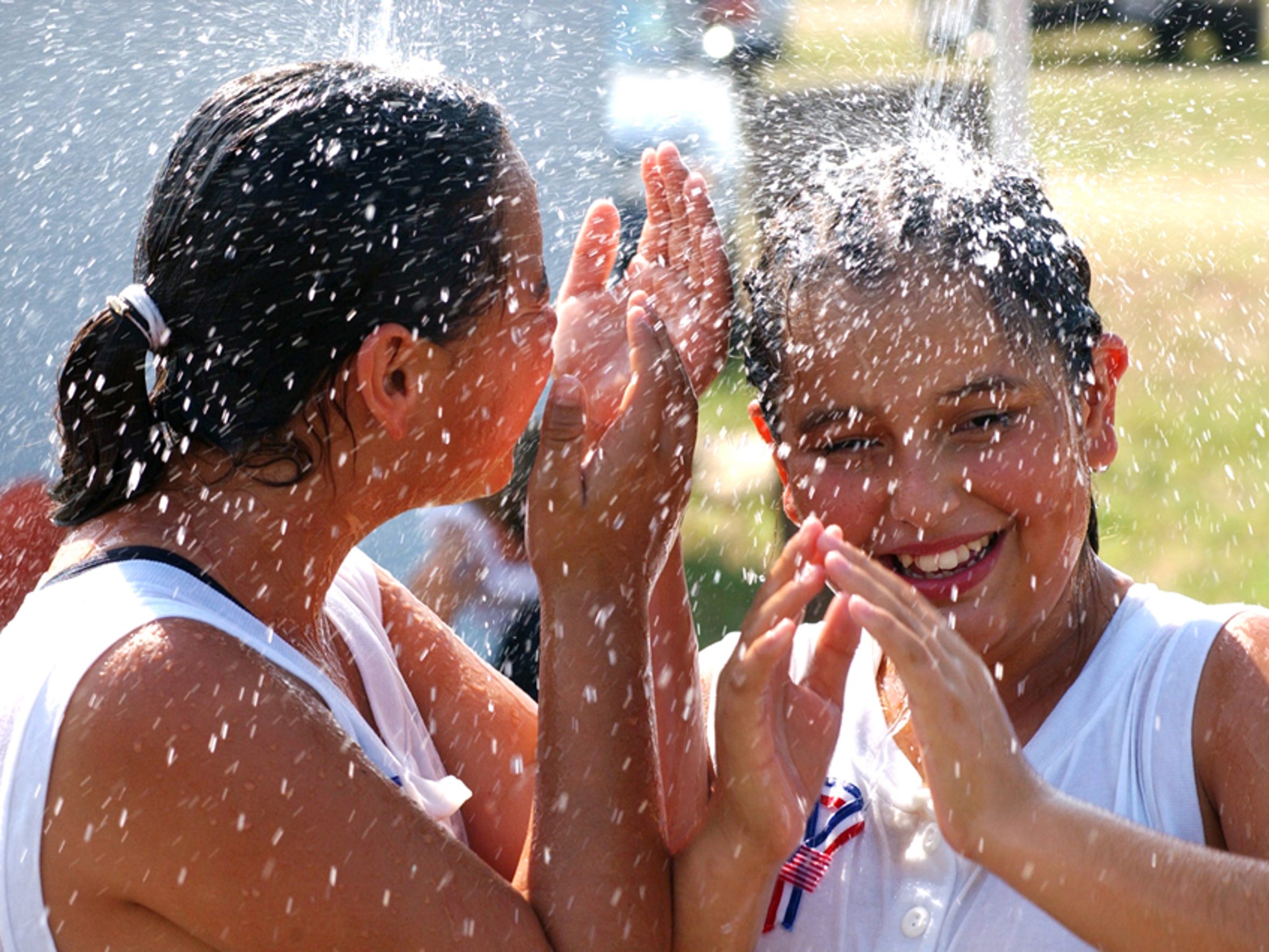 From the left, Leslie Pena and Jessica Ramos cool off in some shower sprinklers set up for people to cool off in, during the Little Mill Kickball State Tournament in Flour Bluff.