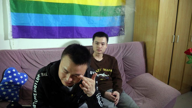 Sun Wenlin, right, sits with his partner Hu Mingliang at home on April 12, 2016, a day before going to court to argue in China's first gay marriage case in Changsha in central China's Hunan province.