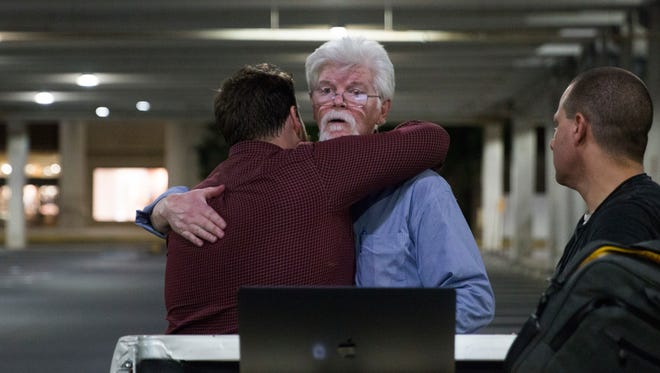 In this June 28 photo, The Capital Gazette reporters Pat Furgurson, center, and Chase Cook hug at a makeshift office in a parking garage of a mall in Annapolis, Md., during coverage of the fatal shootings that happened in their paper's newsroom earlier in the day.