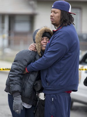 Carmon Lisenby (left), and Corey Bryant, both family members, console each other near 3145 North Harding Street, at a scene involving one male and three female homicide victims, Tuesday, March 24, 2015.