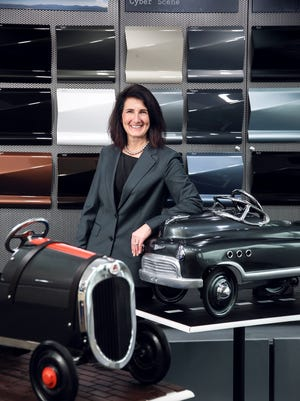 """Nancy Lockhart, Color Marketing Manager, stands next to two pedal cars painted """"Gallant Gray"""" as the """"Automotive Color of the Year for 2017"""" at Axalta Coating Systems in Clinton Township on Tuesday January 3, 2017."""